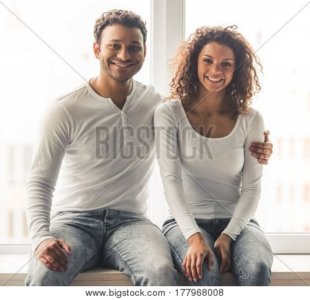 Beautiful young Afro American couple is looking at camera and smiling while sitting on the window sill at home