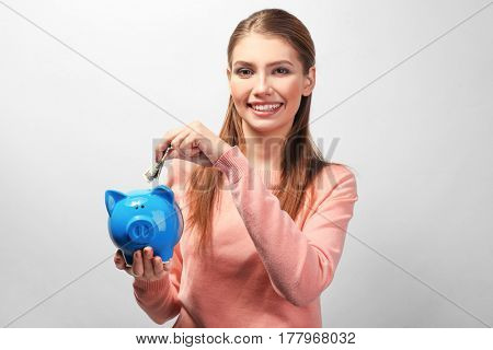 Beautiful young woman putting money into piggy bank, on light background
