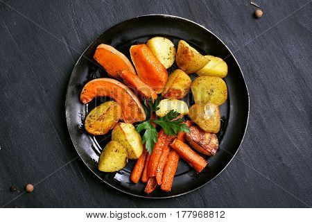 Roasted vegetables on plate on dark background with copy space top view