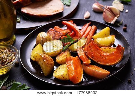 Cooked vegetables on dark plate close up view
