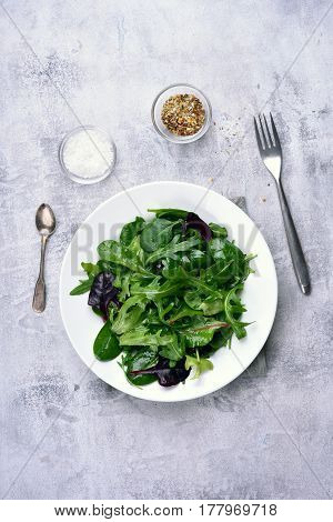 Salad with green leaves of spinach arugul on light stone background. Healthy food top view