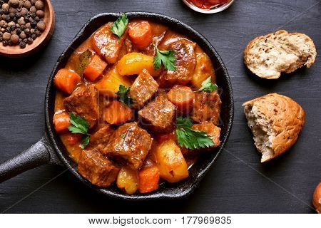 Goulash beef stew in cast iron pan on dark background top view close up