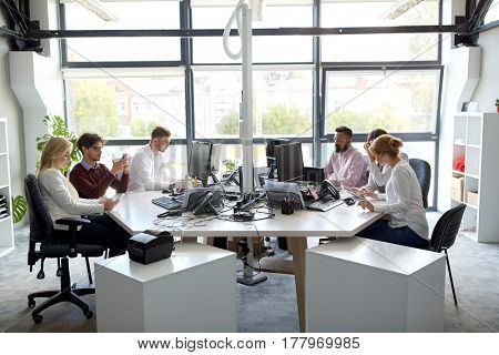 corporate, technology and people concept - business team with smartphones and computers working at office