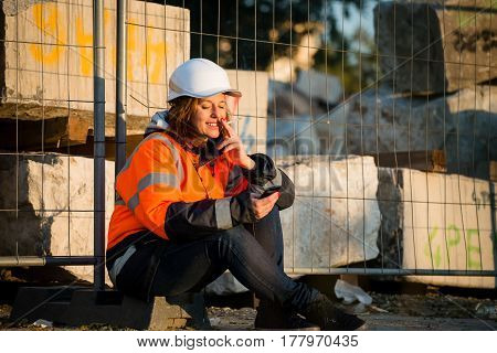 Senior woman engineer in protective workwear relaxing during break, smoking cigarette and looking to mobile phone