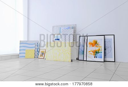 Set of modern paintings on floor at white wall