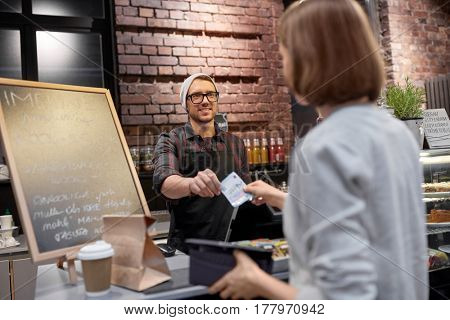 small business, payment, people and service concept - happy barman and woman with wallet paying money at cafe