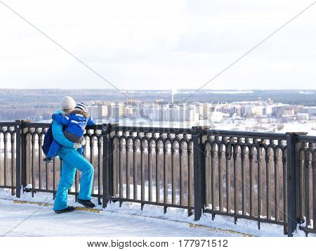 Vladimir -12 February 2017: Mom and child in blue winter clothes watching from the observation deck on the winter city landscape 12 February 2017 Vladimir Vladimir Region Russia
