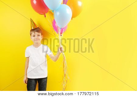 Cute birthday boy with colorful balloons on yellow background