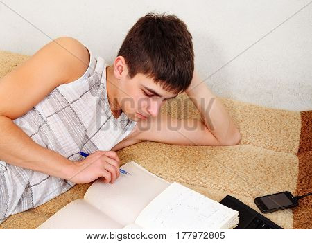 Teenager doing Homework on the Sofa at the Home