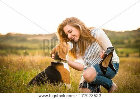 Young woman having fun with beagle dog outdoor in nature on  summer evening, she holds high heels shoes in hands