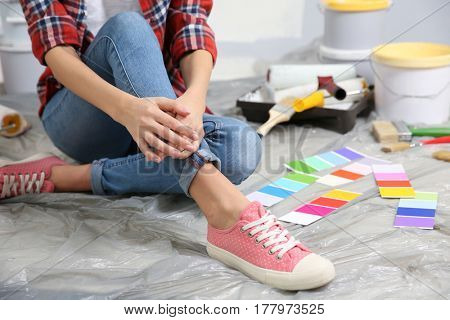 Young female worker with tools making repair in room