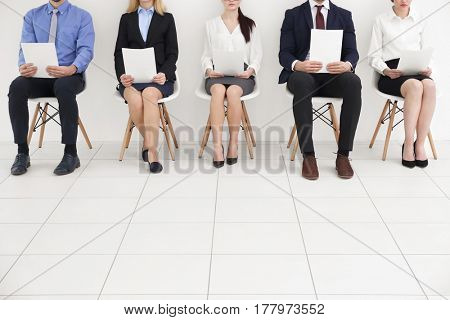 Group of people holding papers and  waiting for job interview on white background