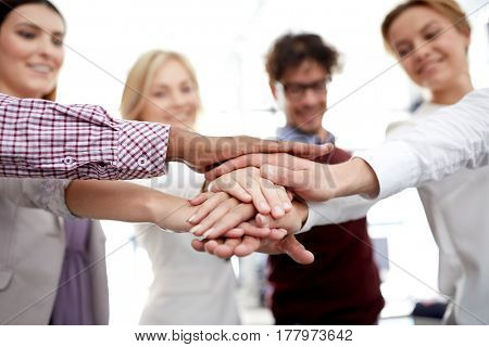 business, startup, gesture, people and teamwork concept - happy creative team with hands on top of each other at office