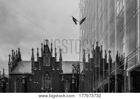 Saint Gertrude protestant lutheran church with reflection in Canada Ambassy building in Riga, Latvia, rainy cloudy sky, black and  white.