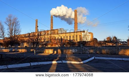 Factory plant puffs smoke stack over blue sky background. Energy generation and air environment pollution industrial scene.