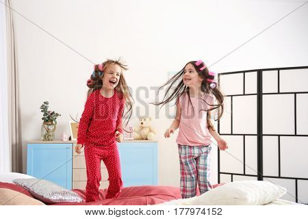 Cute little girls jumping on bed at home