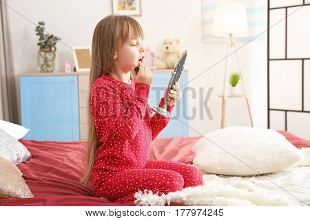 Cute little girl playing with her mother's cosmetic on bed