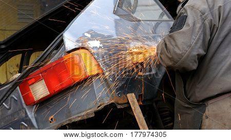 Auto mechanic working on a car body in a car repair shop domestic garage