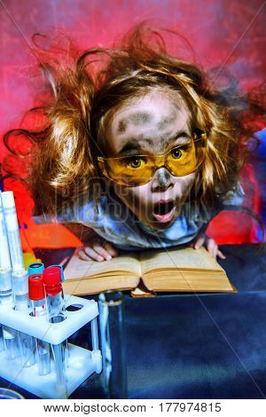 Funny little girl doing experiments in the laboratory. Explosion in the laboratory. Science and education.