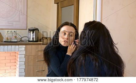 Beautiful brunette woman with long black silky hair puts on and wears earrings and smartens up in front of mirror in make-up dressing room.