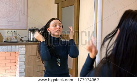 Beautiful brunette woman drying long black silky hair and smartens up in front of mirror in make-up dressing room.