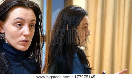 Beautiful brunette woman with long black silky hair talks expressively in front of mirror in make-up dressing room.