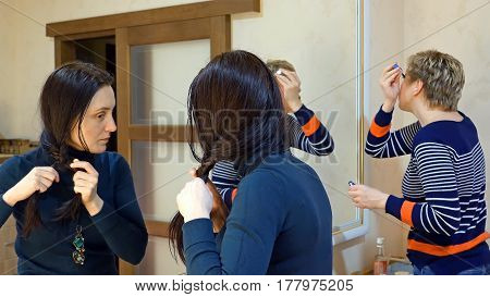 Two beautiful girl friends gossiping chitchatting in dressing make-up room restroom while making up and preparing to go out.