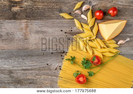 Perfect order of spaghetti, cheese and small tomatoes on the big table, topview