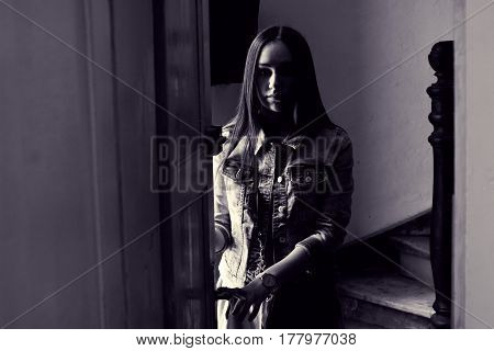 Emotional portrait of girl at door. Beautiful mysterious brunette in dark room. Toned black and white photo