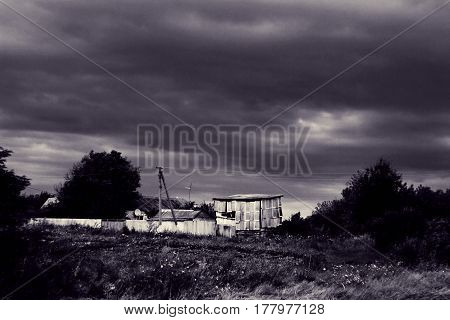 Rural landscape with houses and barn. Village is under dramatic sky. Summer storm weather before rain. Toned black and white photo. Large film grain