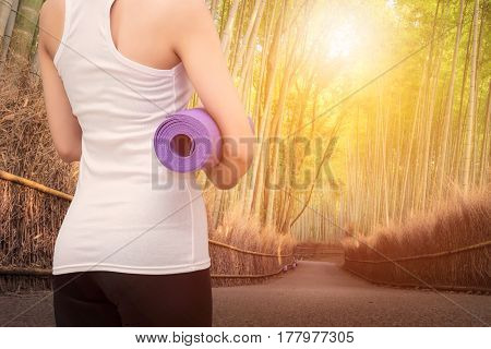 Young asian woman holding her yoga mat in nature bamboo forest. Yoga and meditation have good benefits for health. Photo concept for Yoga Sport and Healthy lifestyle