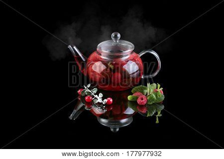 Glass teapot with black tea. Mint cranberry raspberry. On a black background with reflection