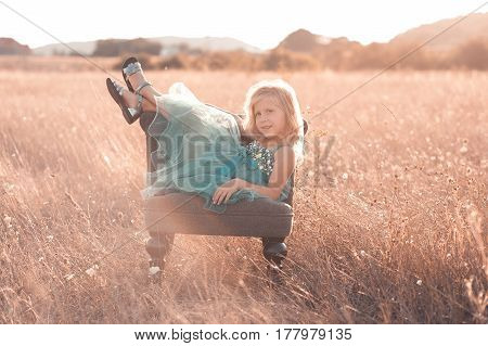 Cute kid girl 5-6 year old sitting in chair in field outdoors. Looking at camera. Childhood. Summer time.