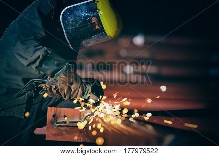 Worker with the face guard to electric wheel grinding on steel structure in factory. add grain filter dark tone heavy work concept.