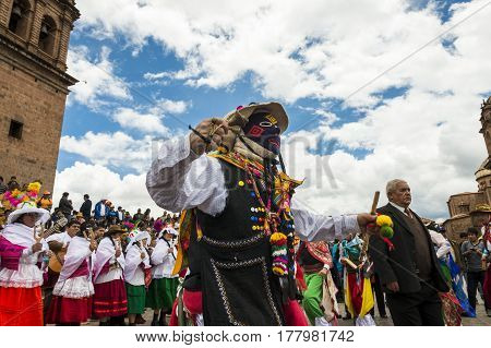 Cuzco Peru - December 25 2013: Man wearing traditional clothes and masks dancing the Huaylia in the Christmas day in front of the Cuzco Cathedral in Cuzco Peru.