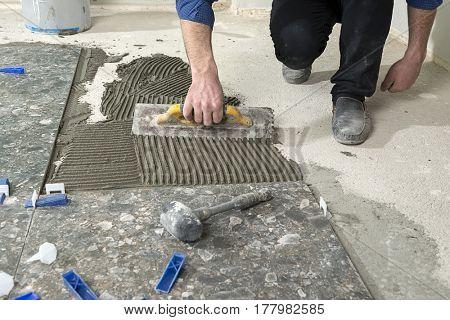 Handyman applying cement adhesive for ceramic tile on floor.