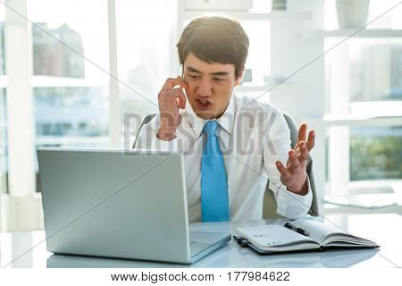 Busy asian businessman working on laptop and calling in office
