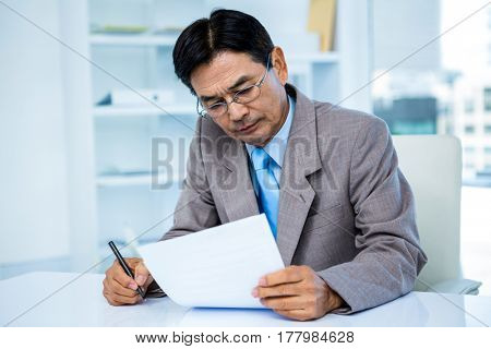 Businessman looking at document in office