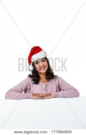 Portrait of woman wearing red Santa hat on table against white background