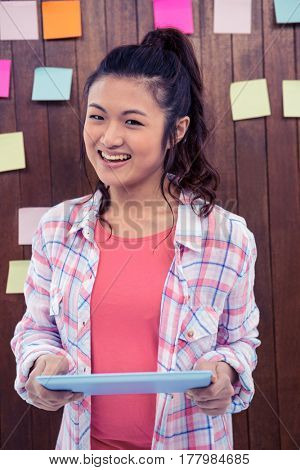 Smiling Asian woman holding tablet