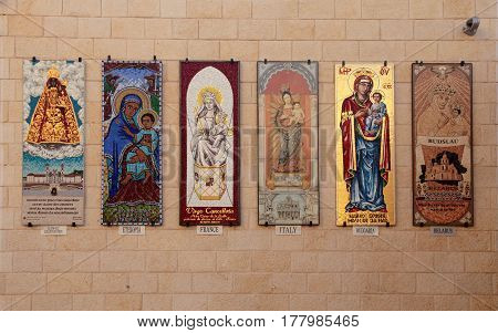 NAZARETH, ISRAEL - AUGUST 30, 2015: The beautiful icon mosaics of Madonna and the Child in different cultural styles on the wall of the Basilica of Annunciation in Nazareth, Israel.