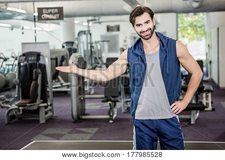 Smiling man showing the gym at the camera