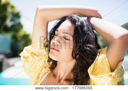 Cheering brunette with closed eyes standing by the pool