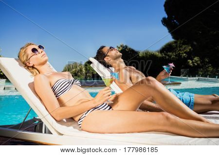 Couple relaxing on deckchairs by the pool