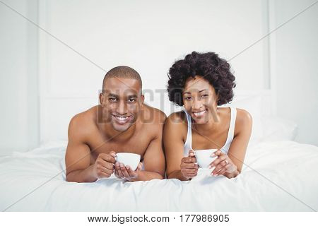 Happy couple lying on bed while holding cups at home