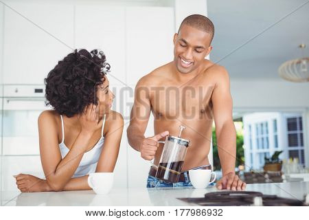 Happy couple drinking coffee in the kitchen at home