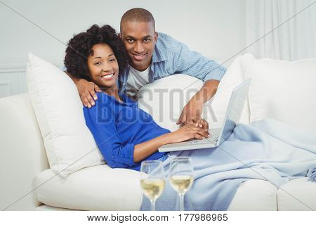 Happy couple on the sofa using laptop with glasss of white wine on table
