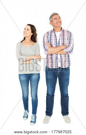 Smiling couple with crossed arms looking away on white background