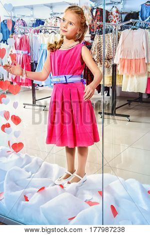 Cute little girl in a beautiful dress posing in the window of children's clothing store. Kid's fashion. Seasonal sale and shopping.