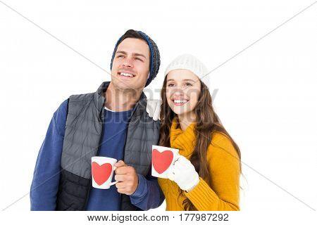 Smiling couple holding mug and looking away on white background